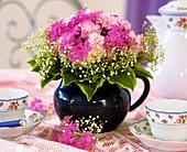 Strauß aus Flammenblumen, Nelken, Schleierkraut & Funkienblatt für die Kaffeetafel