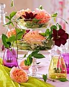 Etagere aus zwei Glasschalen mit Rosen und Clematis