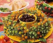 Oliven umgeben von einem Kranz aus Cocktailtomaten