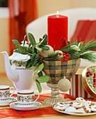Glasschale mit weihnachtlichem Gesteck und Kerze