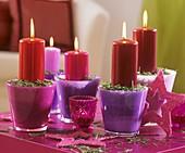 Kerzen mit Tannennadeln in pink und lila Gläsern