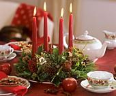 Adventskranz in grün und rot auf weihnachtlichem Teetisch