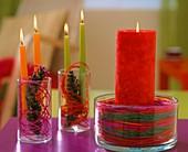 Kerzen in Gläsern mit bunten Peddigrohr