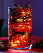 Glas mit Fichtenzweigen, Peddigrohr und Lichterkette