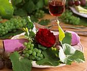 Dunkelrote Rose mit Weintrauben und -blätter als Tellerdeko
