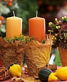 Candles in glass with leaves, moss, ornamental gourds