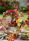 Roses, ornamental apples, Chinese lanterns on tiered iron stand