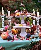 Tiered stand with autumn decorations & petit fours, glass candlestick