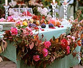 Garland of roses, rose hips and hydrangeas as table decoration