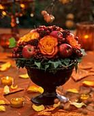 Rosen, Hagebutten, Efeu, Skimmia und Mispel in einer Schale