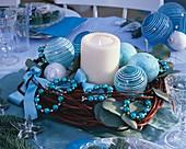 Kerze umgeben von Hartriegel-Kranz mit blauem Baumschmuck