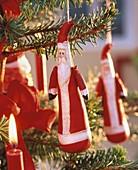 Weihnachtsmann aus Stoff als Baumschmuck an einer Fichte