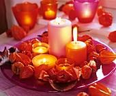 Pinker Glasteller mit Kerzen mit Kranz aus Lampionblume