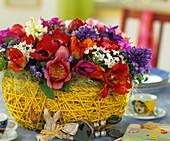 Ostergesteck mit Tulpen, Hyazinthen, Kronenanemone und Milchstern im Korb, Holz-Osterhase liegend