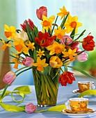 Tulpen und Narzissen in Glasvase