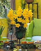 Tisch mit Narzissen, Kaffeetassen und Kleingebäck