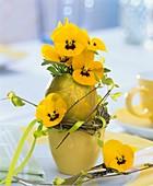 Gelbe Hornveilchen in goldener Eiervase mit Eierbecher