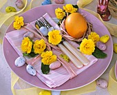 Easter place-setting with primulas, egg and sugar eggs