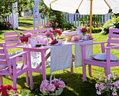 Laid table with peonies and cake in garden