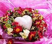 Herz in einem Kranz aus Primel- und Hortensienblüten