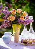 Tisch mit Streuselkuchen und Flieder-Rosen-Strauss im Freien