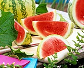Wassermelone, Schnitze und Blätter auf Schneidbrett