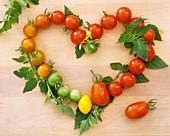 Herz aus Tomaten mit Blättern auf Holzbrett