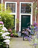 A bicycle in front of a green-painted, English-style door in an inner courtyard with plants