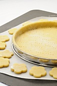Tart tin lined with pastry and unbaked biscuits