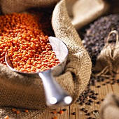 Red lentils in jute sack with scoop