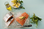 Salmon on crushed ice, olive oil, lemon, bunch of herbs