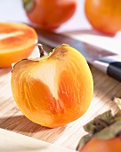 Halved persimmon on chopping board with knife