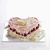 Heart-shaped sponge cake with redcurrants, cream and white chocolate