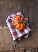 One tomato, variety 'Vintage Wine' on napkin