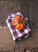 One tomato, variety 'Vintage Wine' on napkin