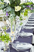Table laid for special occasion with glass tableware and flowers