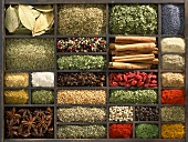Various dried herbs and spices in type case (overhead view)