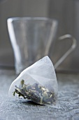Lemon grass tea bag in front of glass cup