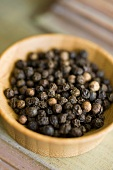 Black peppercorns in a small wooden dish