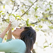 Woman smelling white blossom on tree