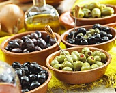 Various types of olives in terracotta dishes