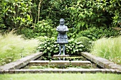 Stone figure by garden pond