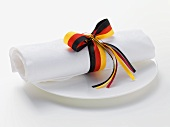 White fabric napkin with ribbon in colours of German flag