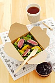 Rocket salad with fried tuna and orange segments in a take-away box