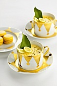 Lime panna cotta in two cups and saucers with macarons