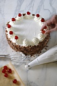Decorating Black Forest gateau with cherries