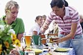 Familie am Tisch beim Sommerfest im Freien