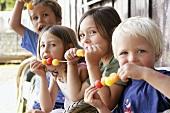 Vier Kinder essen Melonen-Spiesse