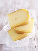 Pieces of Gouda cheese, stacked, on paper