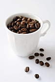 Coffee beans in and beside cup